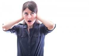 woman covering her ears and looking shocked
